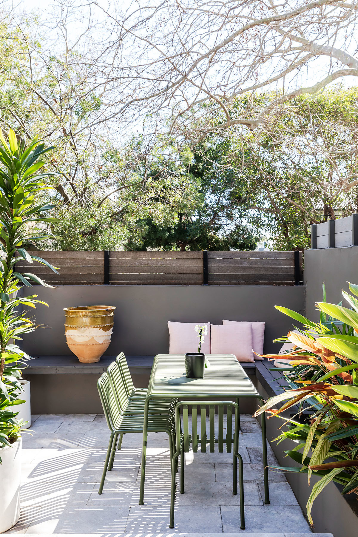 A light, bright living and dining space flows out on to a lush green courtyard. HAY Outdoor Furniture | Custom Bay Seating.