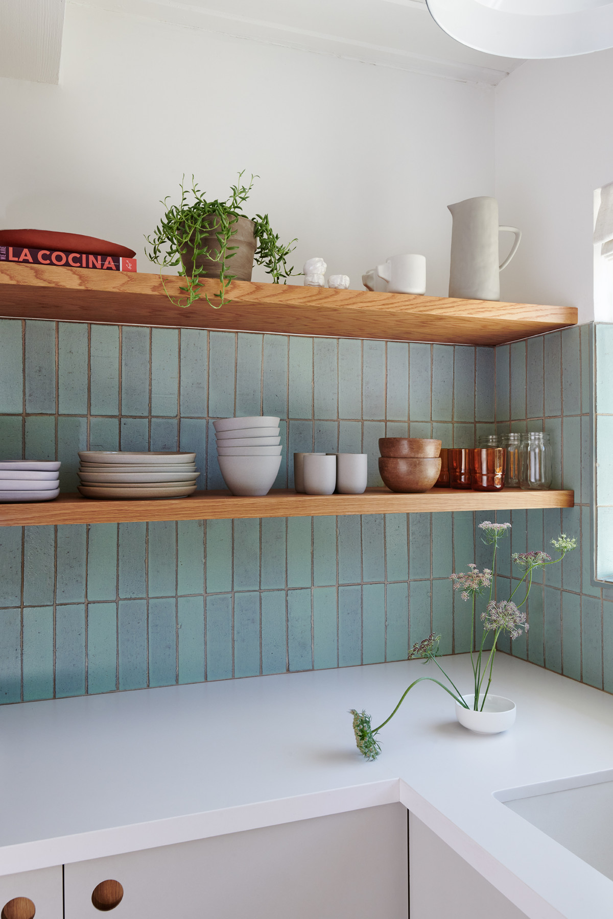 The turquoise-hued backsplash harkens back to her Southwest upbringing while the shelves are filled with items by local artisans and from her visits to Mexico.Fireclay Tile |Earthtones Studio| Mexico-Sourced Bowls And Dishes|Our Place Glasses | La Cocina Cookbook|Blk Girls Greenhouse Plant|Pink Paloma Arrangement.