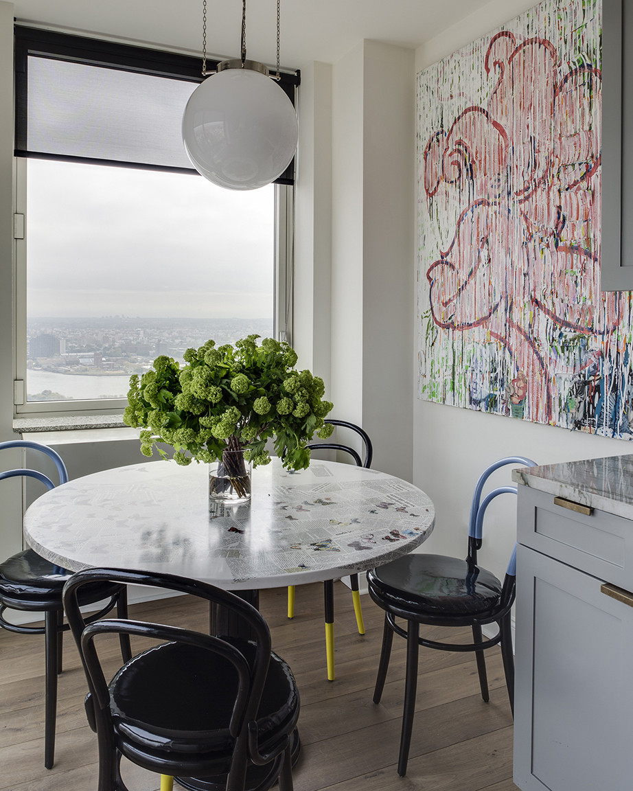 In the kitchen's dining area, a set of paint-dipped Thonet chairs add an unexpected hit of color.