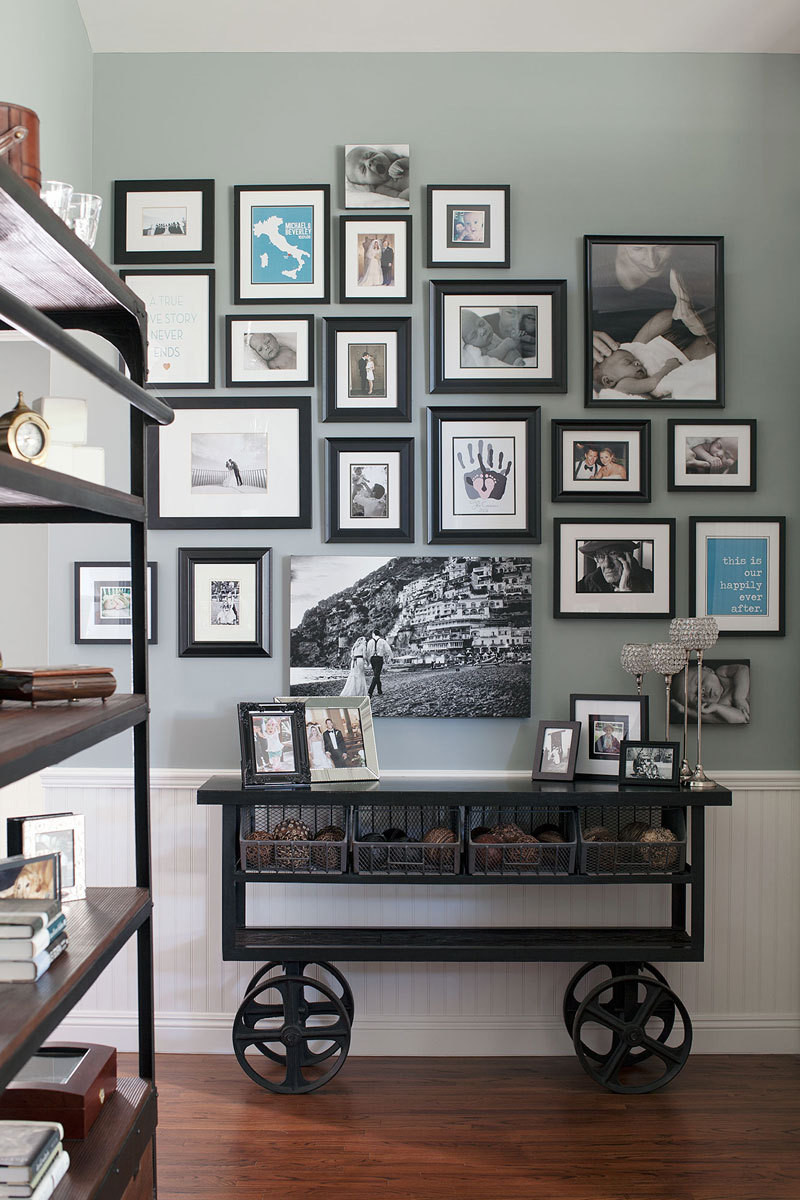 A gallery wall of family photos and meaningful prints takes pride of place above an antique-reproduction iron cart from Arhaus.