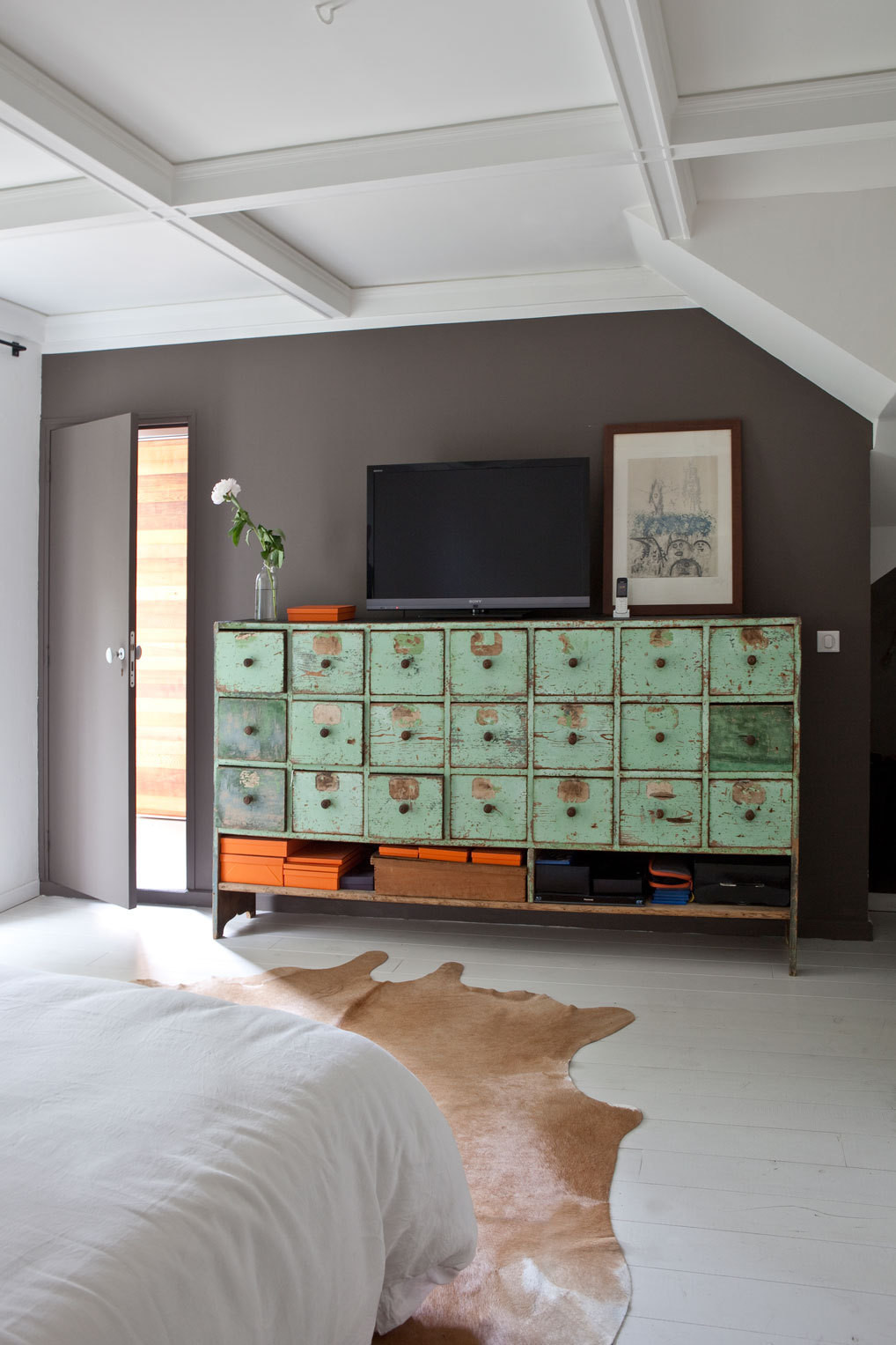 A green chest of drawers found in L'Isle-sur-la-Sorgue pops against a gray accent wall in the master bedroom.