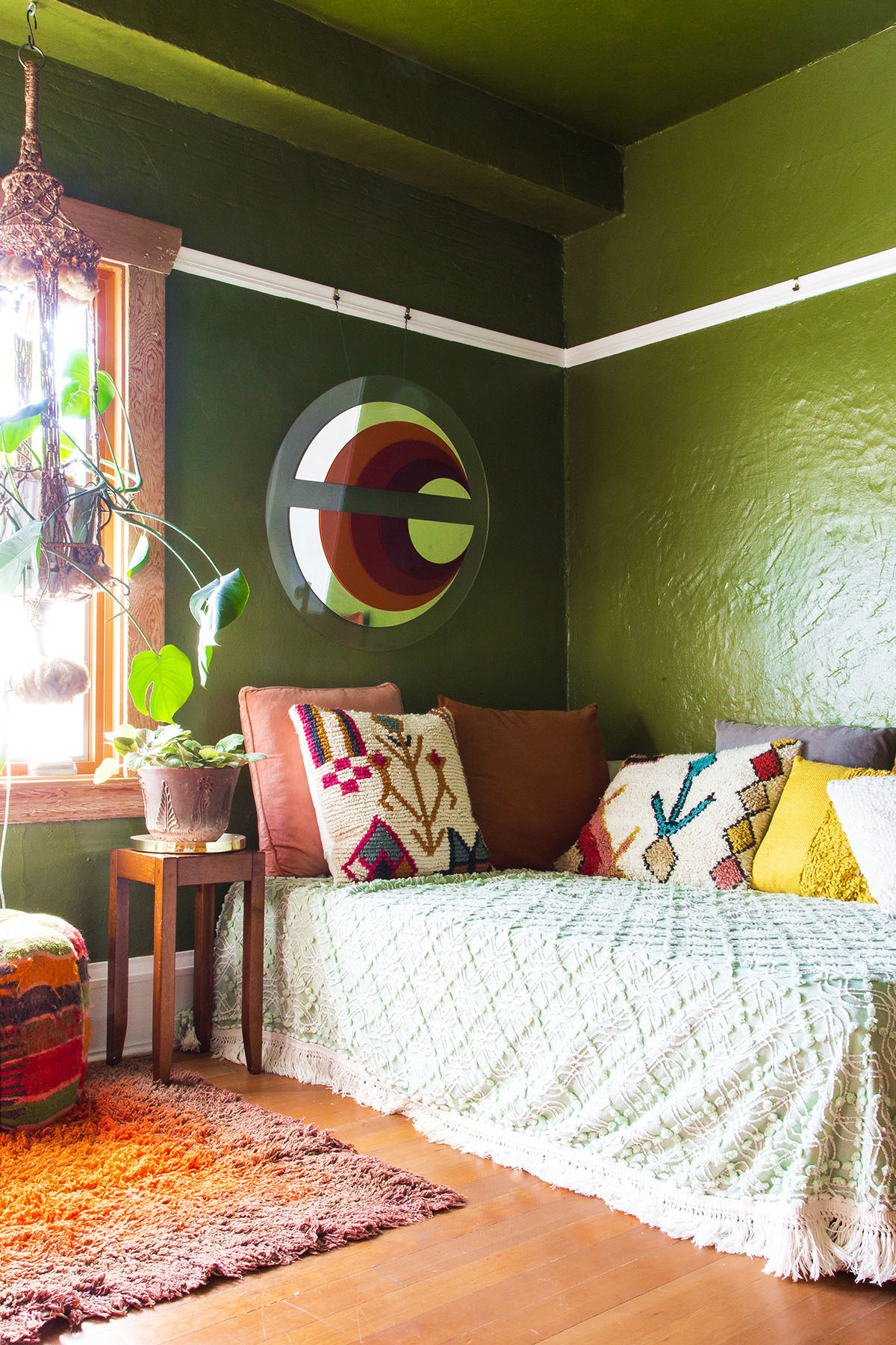 In the sitting room — a cozy space awash with olive green paint — a mirrored artwork dating back to the 1970s holds pride of place.Home Depot Paint | Vintage Bed | Vintage Bedding | Vintage,World Market Assorted Pillows.