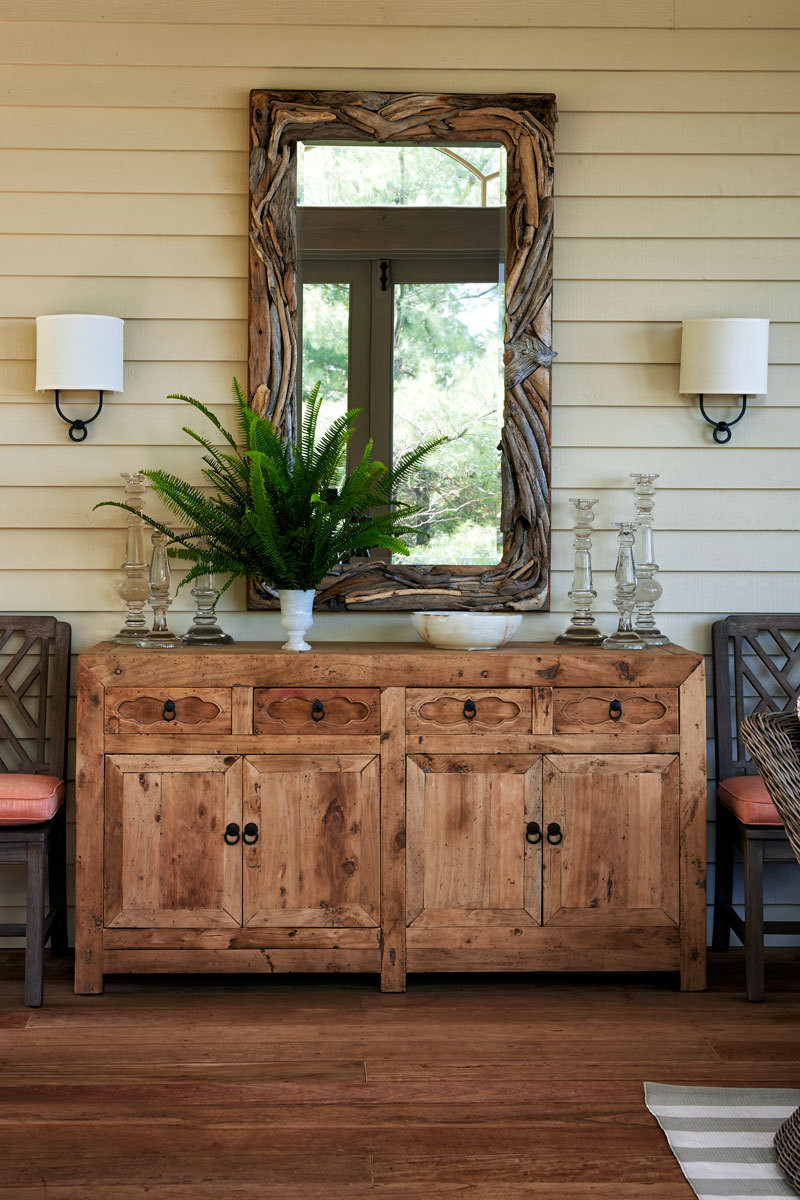 A driftwood mirror by local artist Paul Allen and an Indonesian buffet anchor one side of the screened porch.
