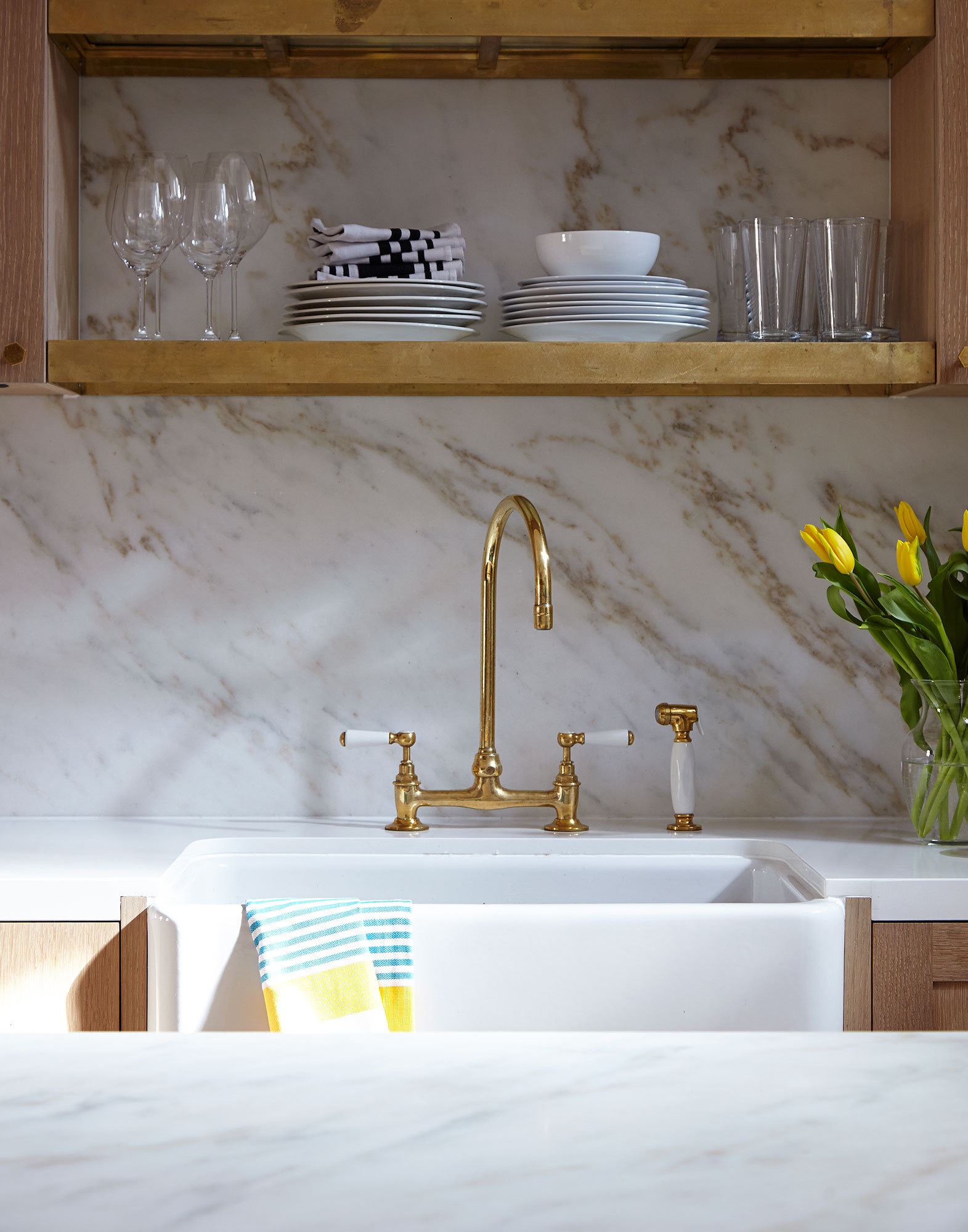 A brass-and-ceramic faucet by Barber Wilsons and Rohl farmhouse sink blend with white Celador outer countertops.