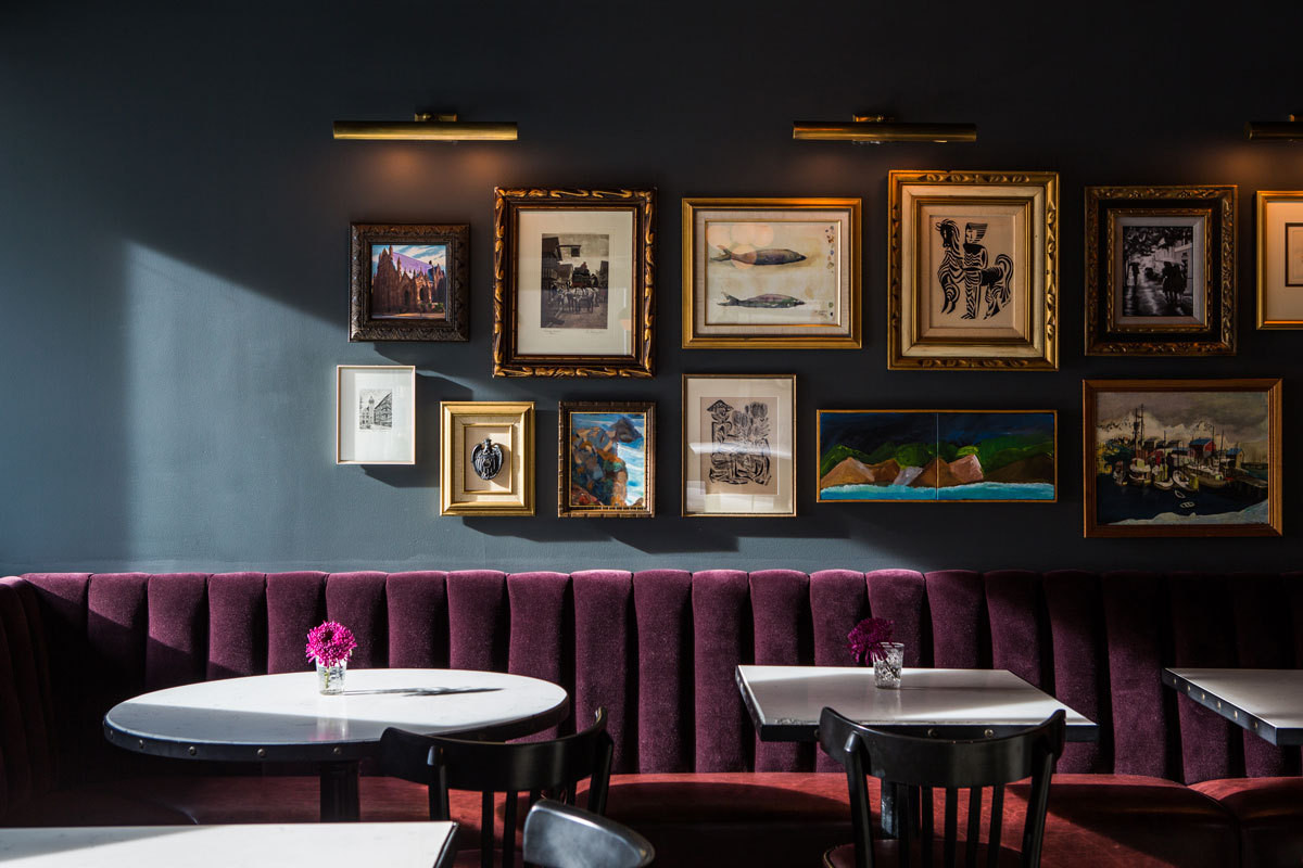 An aubergine-velvet banquette and slate-hued wall make for a cinematic backdrop at Pennyroyal, the bar at Seattle's Palladian hotel.