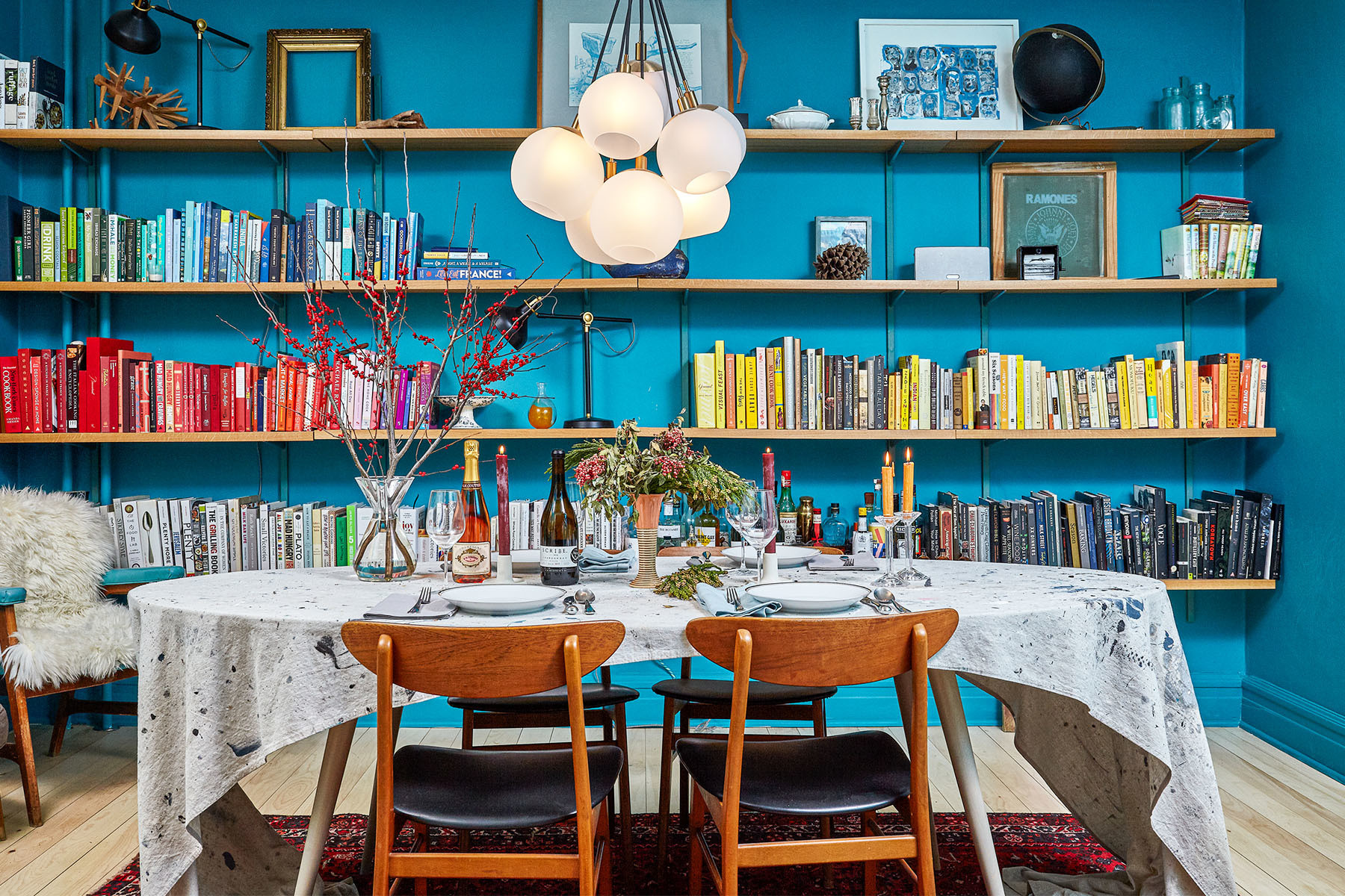 New York-based cookbook author and passionate home cook Colu Henry admits the dining room is her favorite space, awash in turquoise paint. Benjamin Moore Paint | CB2 Chandelier | Vintage Armchair | Sheepskin Town Sheepskin | Sferra Napkins | Crate & Barrel Cutlery | Laguiole Steak Knives | Danica Design Candles | Chad Silver Design Dining Table | Chairish Dining Chairs | Chad Silver Design Tablecloth | Jenni Kayne Candlestick Holders | Vintage Accent Pieces | Vintage Silkscreen | Andy Wilhelm Artwork | Vintage China.