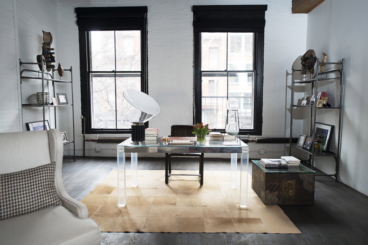 A cowhide rug grounds a sleek black-and-white study space.