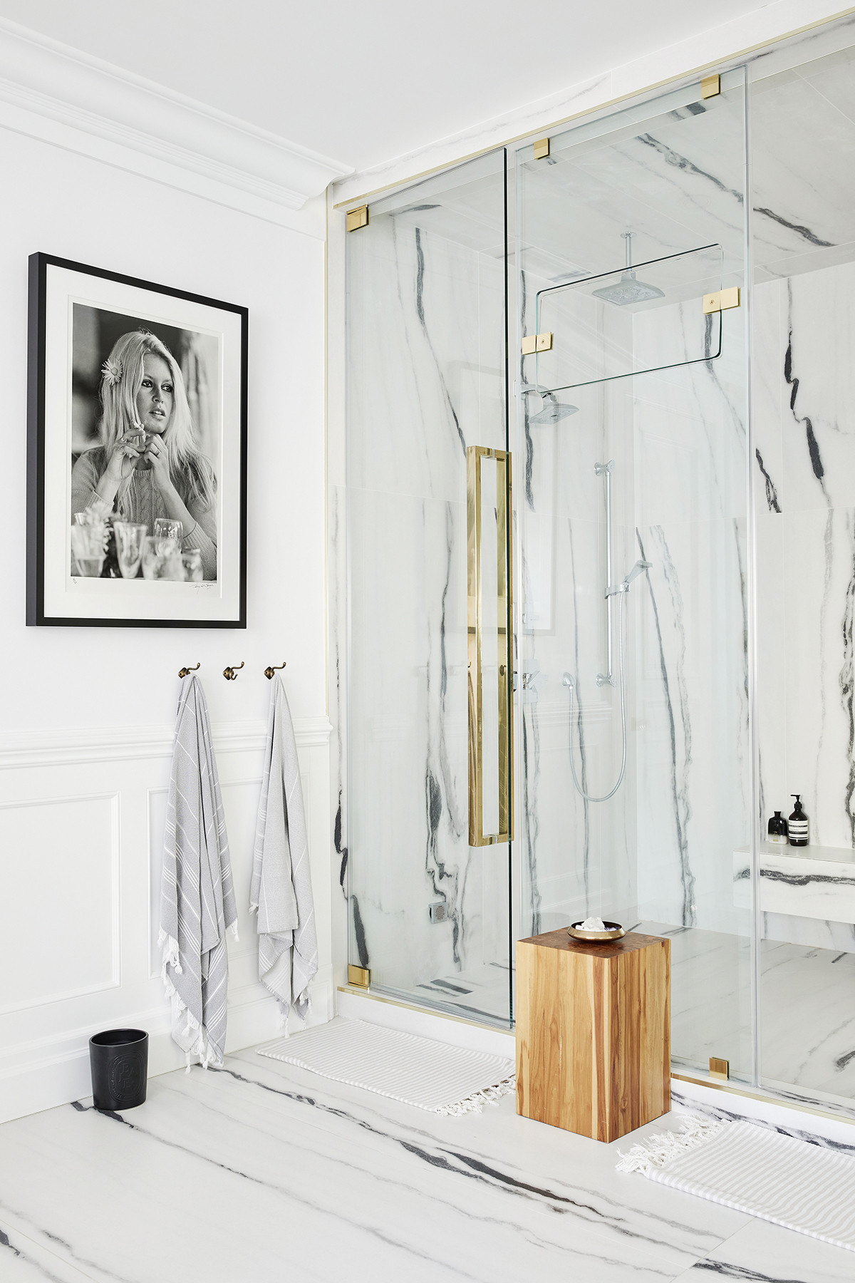 This marble spa shower is what bathroom dreams are made of complete with a stone bench to inspire completerelaxation.AesopGeranium Leaf Body Cleanser |DiptyqueBaies Ceramic Candle |Bertu HomeModern Wood Side Tables.