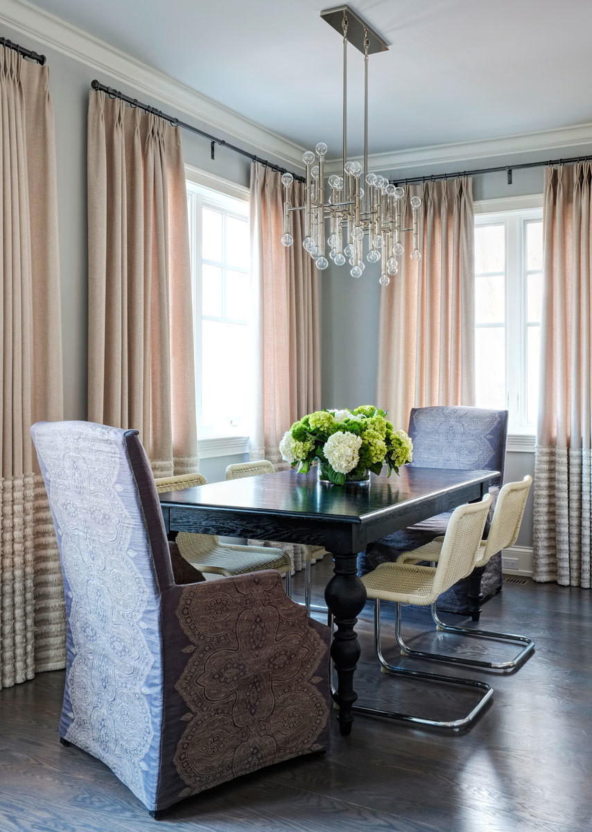 Stately slipcovered armchairs compliment curvaceous midcentury-style seats at the dining table.