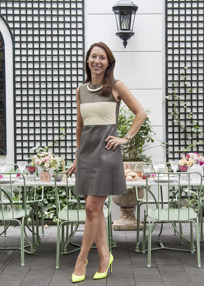 Ladurée Co-President Elisabeth Holder Raberin in the brand's Soho garden wearing a Céline dress, Saint Laurent Paris shoes, and Aurélie Bidermann jewelry.
