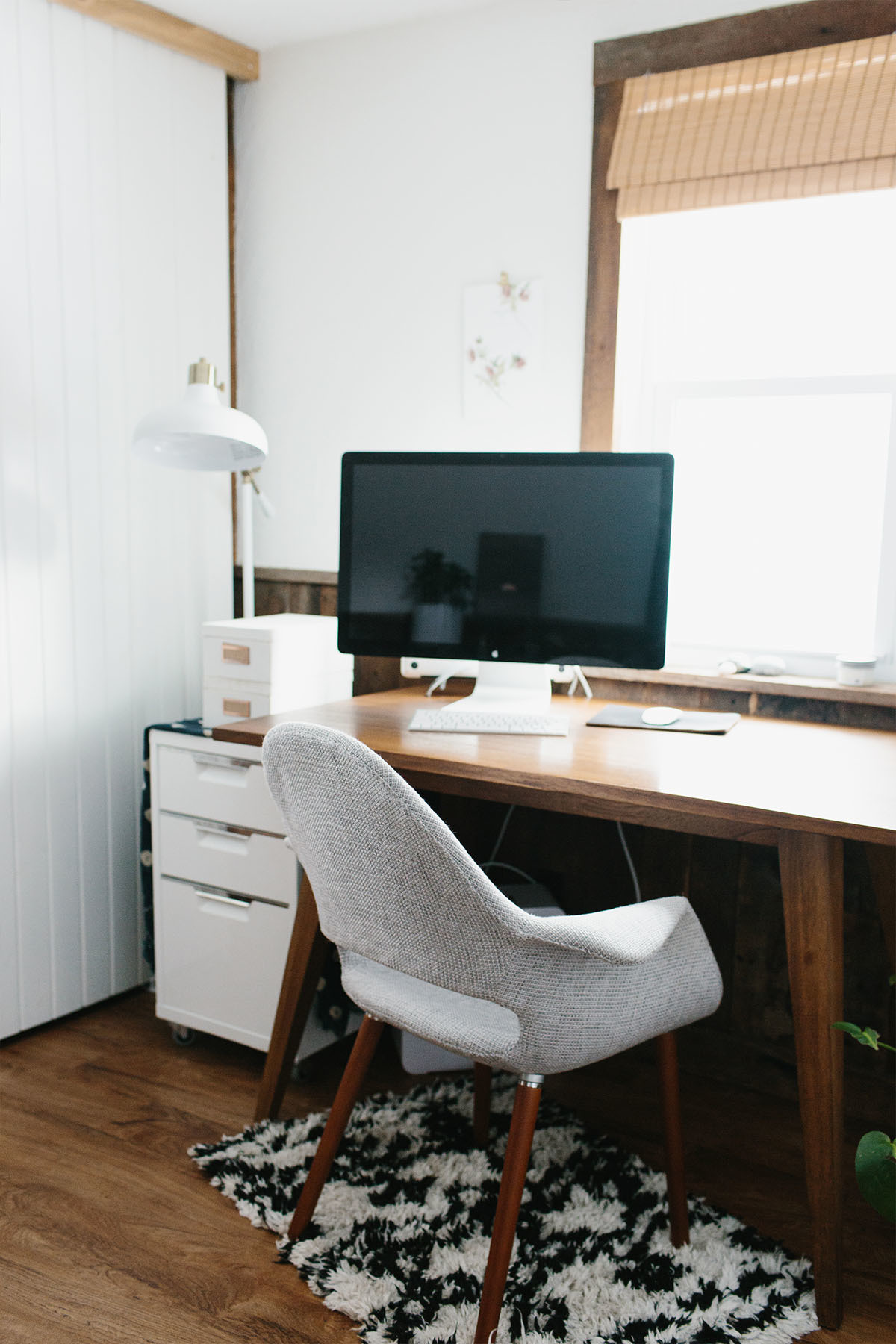 To comfortably work from home, Stier created a cozy study nook within her cottage. West Elm Desk | CB2 Side Table | Darling Botanicals Co. Plant | Spencer Arthur McQueen Artwork | Target Rug | Apple Mac Computer | IKEA Lamp.