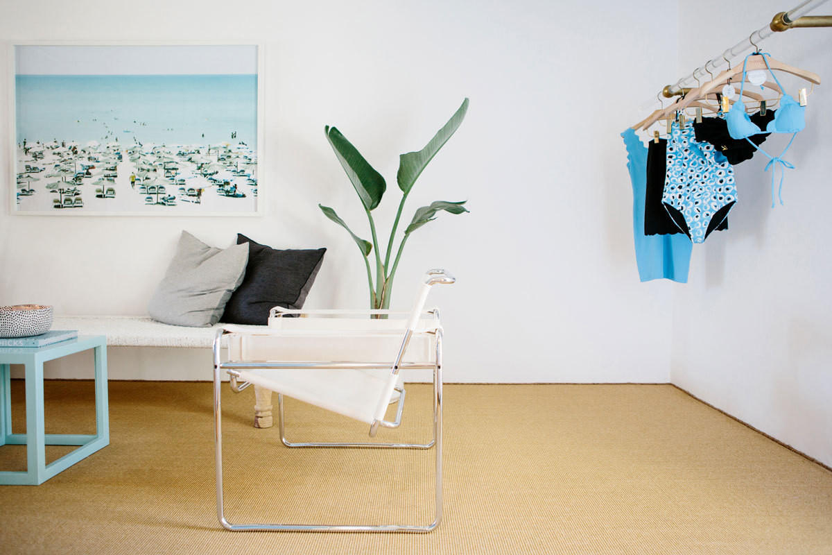 A floating rack of blue and black swimsuits overlook the casual sitting area of Marysia Swim's California studio office.