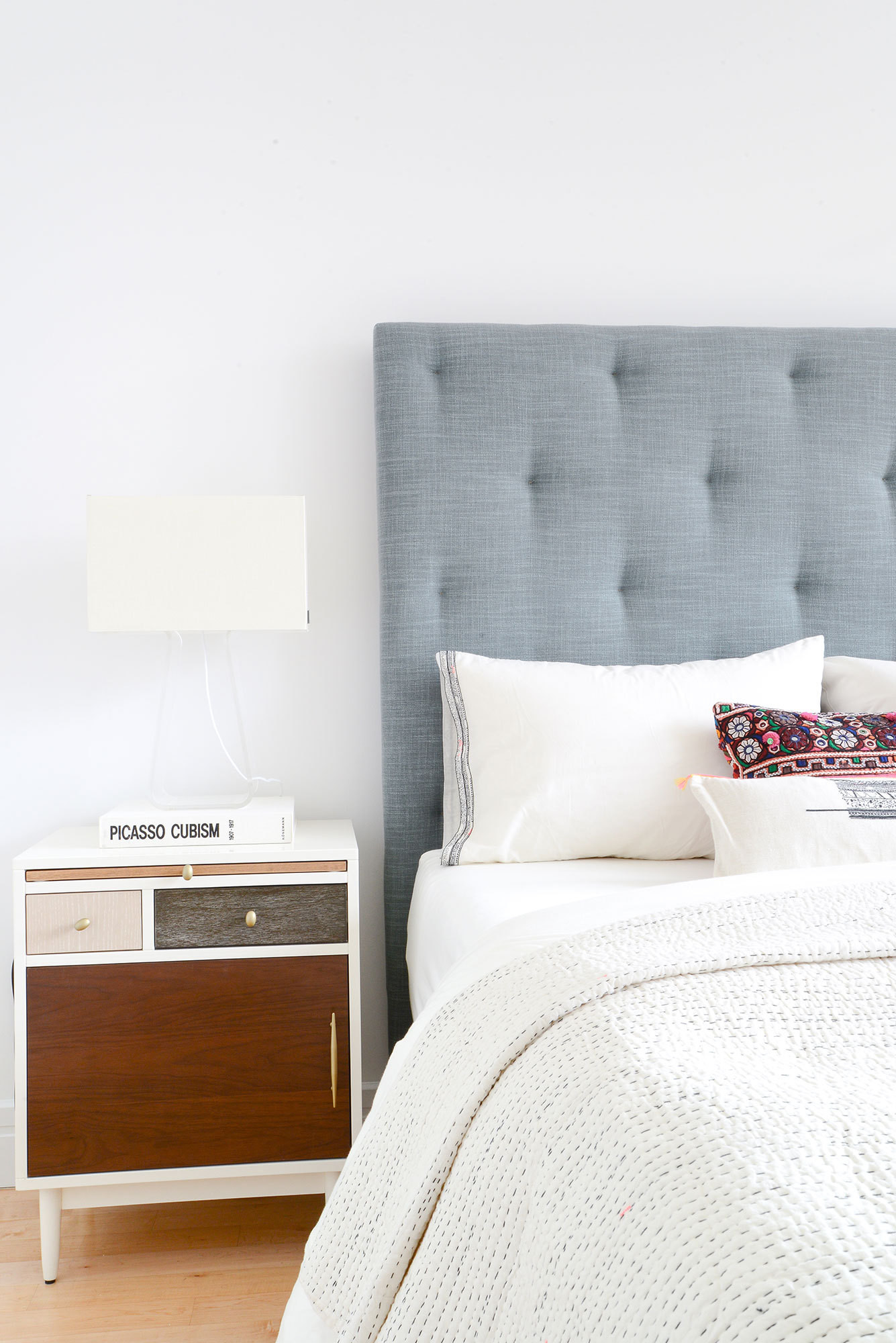 The bedroom features a more monochromatic palette, with a gray tufted headboard as a neutral anchor.